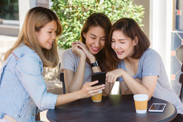 Cheerful asian young women sitting in cafe drinking coffee with friends and talking together. Attractive asian woman enjoying coffee while using smartphone for talking, reading and texting.