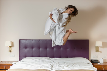 Funny young woman jumping on white bed