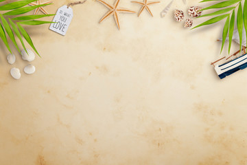 Top view of seashells various kinds, palm leaves, sailboat and starfish on old paper. Flat lay. Travel concept, empty space for text