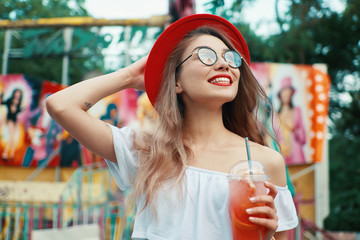 Beautiful young woman holding a drink while smiling