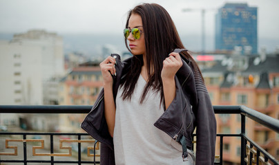 Stylish young woman in sunglasses posing in leather jacket on urban background