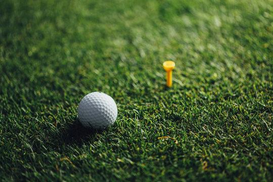golf ball nearby yellow tee on green grass, closeup view