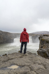 Iceland, North of Iceland, young man looking to waterfall