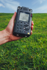 portable audio recorder in hand field recording ambient sounds of nature