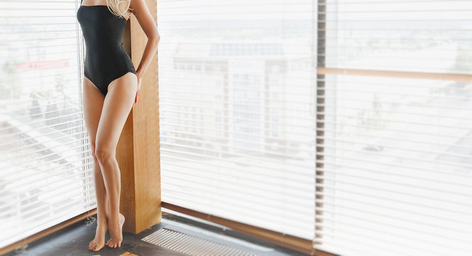 Sexy unrecognizable woman in bodysuit stands near the window.