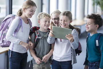 Laughing pupils looking at tablet on school corridor