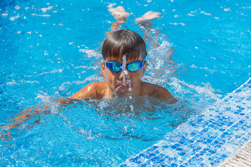 Boy spitting water, summer games at pool. Copy space.