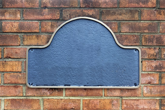 Blank plaque secured to ageless brick wall.