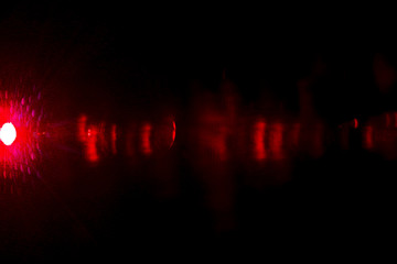 Camera lens flare by laser light create effect depending of iris shapes and interference effect and moire on digital sensor on dark black background
