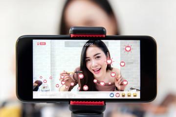 Asian woman beauty vlogger sharing makeup tutorial video on social media