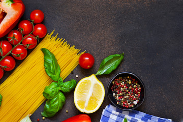 Italian food background. Ingredients for cooking pasta: spaghetti, tomato, basil and pepper on a dark concrete background.