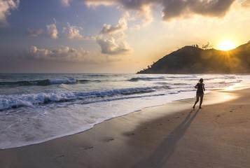 girl running through sandy ocean seashore at sunrise in phangan island
