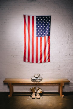close up view of american flag hanging on white brick wall and arranged military uniform on wooden bench
