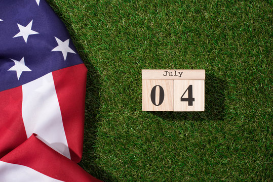 top view of american flag and wooden calendar with 4th july date on green lawn, americas independence day concept