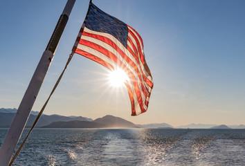 Stars, Stripes and Sun Star -  The American Flag is spotlighted by a star burst from the sun. Alaskan ferry. Haines, Alaska.