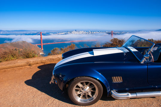 Vingtage classic sport car with San Francisco Golden Gate bridge on foggy background view from Marin Headland