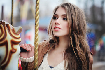 Happy young woman in merry-go-round outdoors. Beautiful girl portrait
