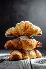 three croissants on dark wooden background close-up