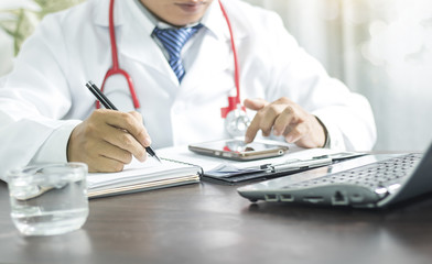 doctor writing information  on notebook and looking at phone for planning to take care good healthy