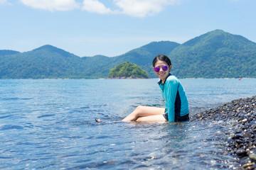 Beautiful woman sitting on the beach. Lipe island Thailand.