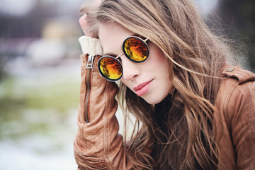 Young woman in sunglasses, outdoors portrait