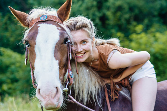 Portrait of happy smiling woman cowgirl, riding a brown horse. Clothed white jeans shorts, brown leather vest. Has slim sport body. Portrait nature. People and animals friendship concept.