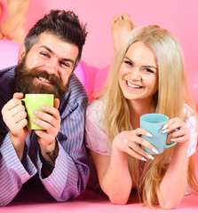 Couple relax in morning with coffee. Family tradition concept. Couple in love drink coffee in bed. Man and woman in domestic clothes, pajamas. Man and woman on smiling faces lay, pink background.