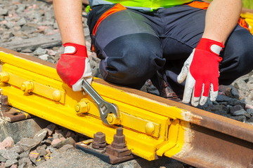 Worker with adjustable wrench fixing screw nut on railway track