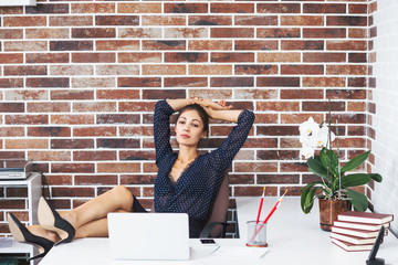 Business woman with legs on the desk in office looking to laptop