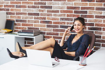 Relaxed business woman with legs on the desk in office