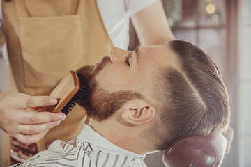 Spoed Fotobehang Kapsalon The barber combs the man's beard with a brush. Photo in vintage style
