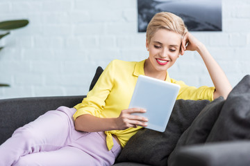 happy young stylish woman using digital tablet on sofa at home
