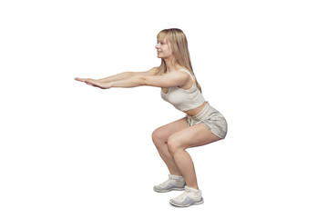 Sportive blonde gymnast in the sportswear squats on the white background in the studio. Shoot from the side. . She holds her hands raised. Coach in shorts and a white t-shirt