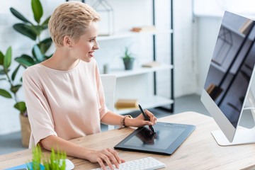side view of smiling female freelancer drawing on graphic tablet at table in home office