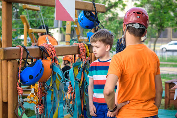 Instructor helping little boy to put helmet and safety belts to participate in rope park.