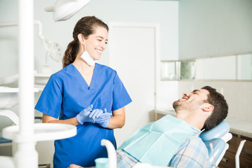Smiling Dentist In Scrubs Talking To Patient At Clinic