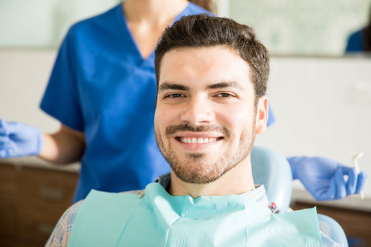 Smiling Man With Dentist Holding Dental Tools At Clinic