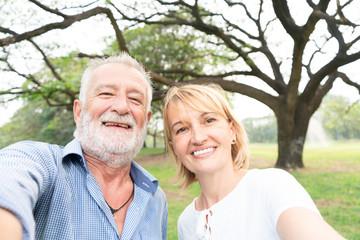 Elderly couple taking selfie in park