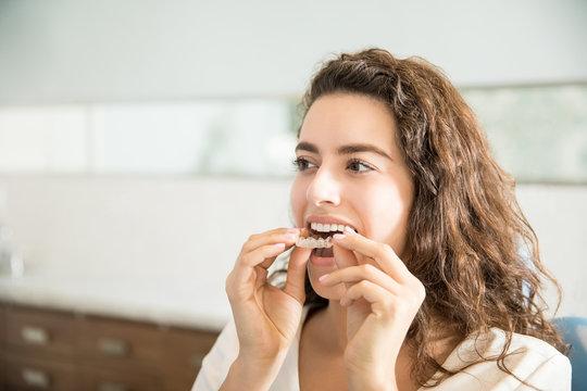 Woman Wearing Clear Aligner In Dental Clinic