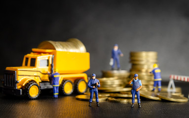 miniature security guard officers standing and protection in front of dumper truck loading the golden coins. money security protection concept