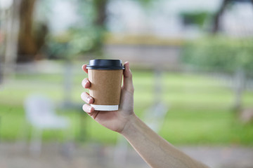 Disposable White Coffee Cup with Black Lid holding on hand for takeaway on a blur green Background