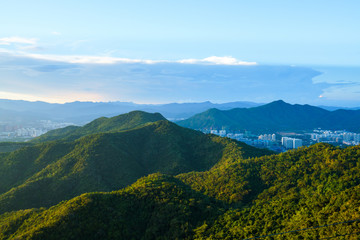 Green mountains in landscape with city