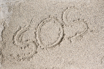 The words SOS are written on the sand