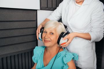 Doctor preparing senior patient to hearing exam in special audio room