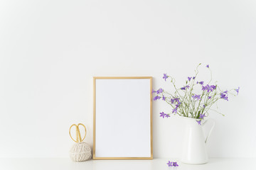 Gold portrait frame mockup with wild flowers in vase near white wall. Empty frame mock up for presentation design. Template framing for modern art.