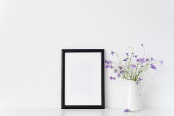 Black portrait frame mockup with wild flowers in vase near white wall. Empty frame mock up for presentation design. Template framing for modern art.