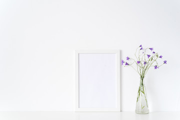 White portrait frame mockup with wild flowers in vase near white wall. Empty frame mock up for presentation design. Template framing for modern art.