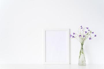White portrait frame mockup with wild flowers in vase near white wall. Empty frame mock up for presentation design. Template framing for modern art.