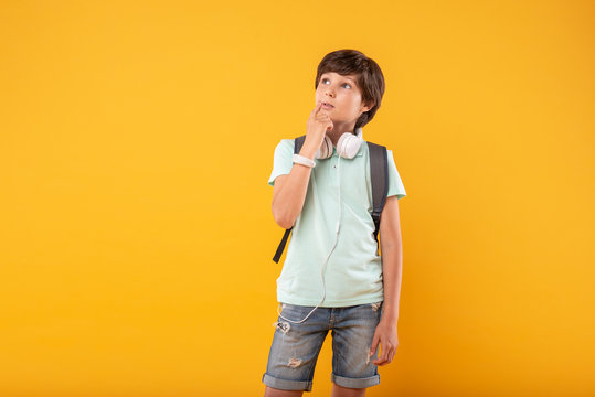 Second thoughts. Serious dark-haired boy wearing headphones and a schoolbag and thinking