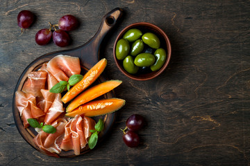 Jamon serrano or prosciutto with melon and olives over rustic wooden background. Italian or spanish antipasti, appetizer board